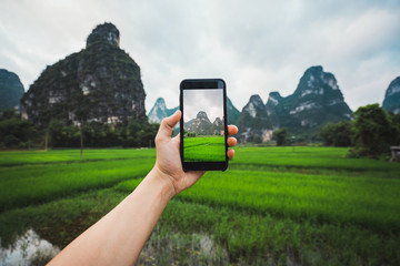 Crop hand taking photo in rice fields of Chinese Guangxi