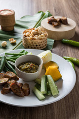 Thai northern food. Nam Prik Num (Northern Thai Green Chilli Dip), Streaky pork with crispy crackling, Sai aua (spicy sausge) and vagetable