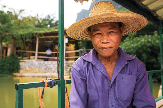 Portrait of fisherman in straw hat sitting outdoors