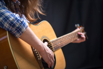 Girl teenager playing an acoustic guitar on a dark background in the Studio. Concert young musicians