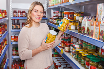 Female in shop holding pickle goods in grocery section