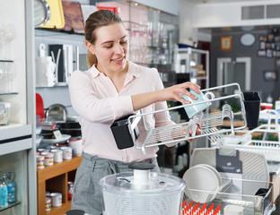 Female buyer choosing kitchen rack in the tableware store