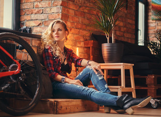 Sensual blonde hipster girl with long curly hair dressed in a fleece shirt and jeans sitting on a wooden box, looking away, at a studio with loft interior.