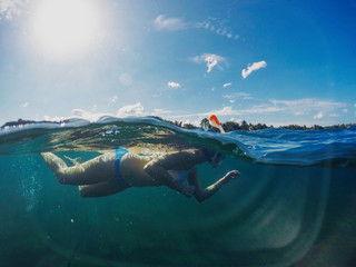 Swimming girl in sunny tropical seashore. Woman swim in blue sea. Snorkeling girl in full-face snorkeling mask.