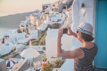 girl tourist photographs phone sunset