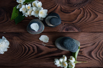 Pyramids of gray zen stones with beautiful fresh white flowers. Concept of harmony, balance and meditation, spa, massage, relax