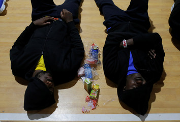 Migrants rest in a sport center after arriving on a rescue boat at the port of Barbate