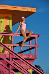 Attractive and sporty swimsuit model sitting at the lifeguard tower.