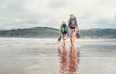 Father with son walk barefoot on the sand ocean beach