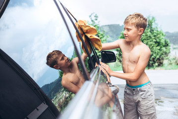 Boy helps with car washing: rubes windows to shine