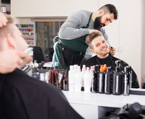 Man hairdresser making haircut to client