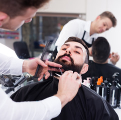 Ordinary guy creating shape for beard of client