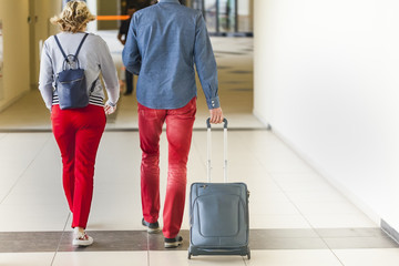 couple of tourists in red jeans with a suitcase at the airport