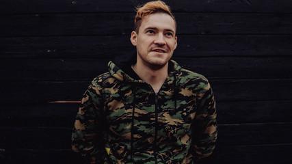 Сохранить Скачать изображение для предпросмотра Guy camo, a man in a hoodie on a black wooden background. Soldiers at the wall