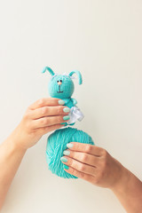 Handmade knitting toy. Female hands with a beautiful blue manicure hold threads and a toy. Soft focus. White background. Free space for text. Concept.