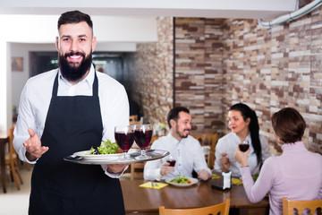 happy waiter serving dear restaurant guests