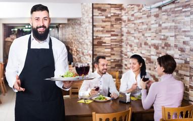 Waiter serving restaurant guests