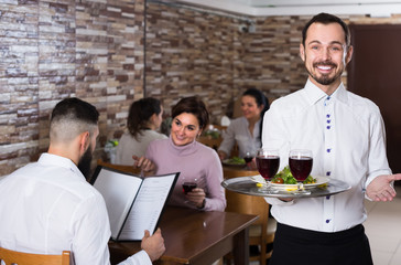 Portrait of adults in middle class restaurant and friendly waiter