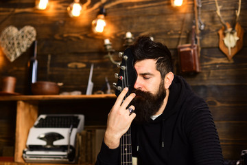 Connection through music. Man bearded musician enjoy evening with bass guitar, wooden background. Guy sits dreamy in cozy atmosphere. Man with beard hugs neck of electric guitar. United with music