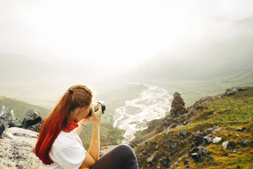 A young girl traveler takes pictures of a summer mountain landscape. Elbrus region, Russia. Woman Emancipation Concept