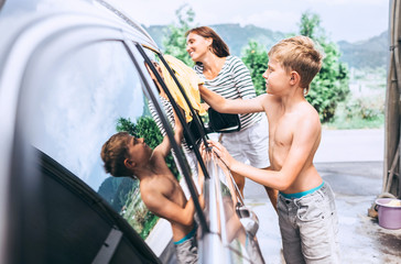 Boy helps to wash a car his mother