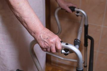 Elderly woman using a walker at home.