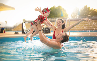 Beautiful family having fun in a swimming pool