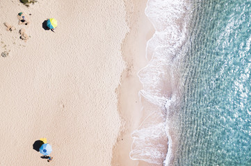 Aerial view of amazing turquoise sea with two coloured umbrellas. Beautiful sunny summer day in Sardinia, Mediterranean sea, Italy..