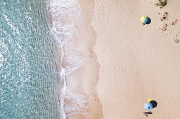 Aerial view of amazing turquoise sea with two coloured umbrellas. Beautiful sunny summer day in Sardinia, Mediterranean sea, Italy.. Wall mural