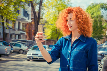 redhead girl making selfie using a smartphone and smiling