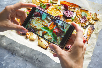 Female hands taking photo of food with mobile phone. Baked vegetables on parchment.