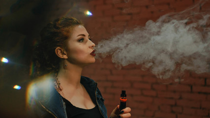 Young attractive red-haired girl smokes an electronic cigarette. She stands by the brick wall. Evening city lights blink.