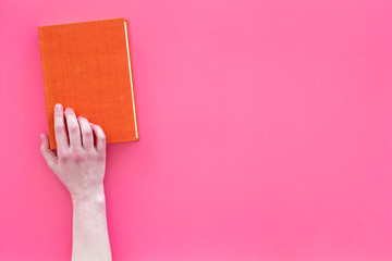Reading concept. Reading as hobby. Hands take hardback book with empty cover on pink background top view copy space