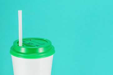 white plastic coffee cup with green lid on a blue background, view from above with copy space