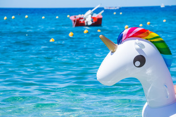 Unicorn swim tube on the beach on sea background. Inflatable rubber unicorn.Fantasy Swim Ring for Summer Pool Trip or swimming in sea, ocean, copy space