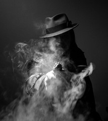 Caucasian Male in vintage trench coat and fedora. Black and white Smoke