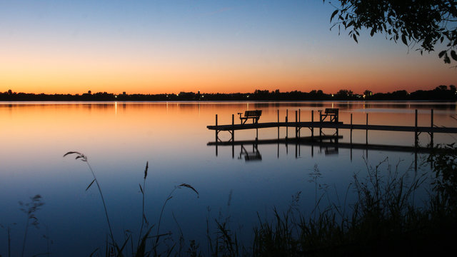 Bemidji, Minnesota, the Best Town in Minnesota is seen across Lake Irving, the first lake on the Mississippi River, after sunset in summertime. A dock is seen in the foreground in this night photo.