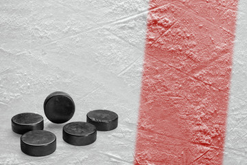 Hockey pucks and a fragment of the ice arena with a red line