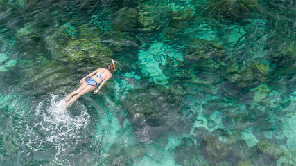 Woman swimming in blue sea. Snorkeling girl in full-face snorkeling mask. Coral reef in shallow sea. Snorkel undersea. Seashore underwater photo. Active seaside vacation. Water sport in tropical sea.