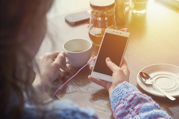 woman using smartphone in coffee shop in cafe with cup of coffee