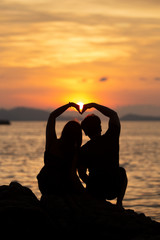 Couple making heart shape on the beach in sunset.