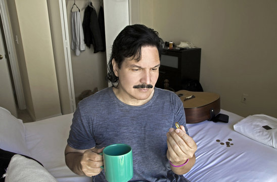 Hispanic man looks at fish oil pill before taking it with beverage