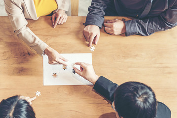 Businessman team work holding two jigsaw connecting couple puzzle piece for matching to goals target, success and start up new project in office.  Business Concept.