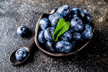 Raw fresh blueberries in small black bowl, dark rusty background copy space