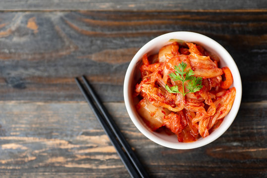 Kimchi cabbage in a bowl with chopsticks for eating on wooden background, top view, Korean food