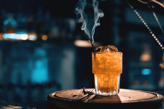 scottish bee cocktail with smoke on blue background;