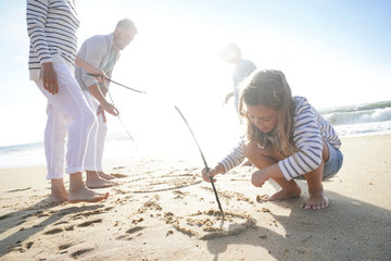 Family having fun writing messages on sandy beach