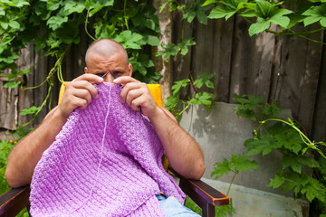 A young bald man sits on an armchair and knits a sweater from natural lilac wool threads at the dacha, in the background a wooden fence, grape bushes