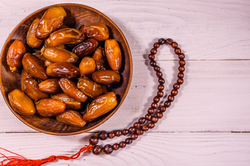 Date fruits and rosary on wooden table. Top view