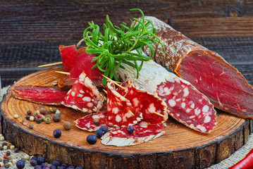Sliced cured sausage and bresaola with spices and a sprig of rosemary.